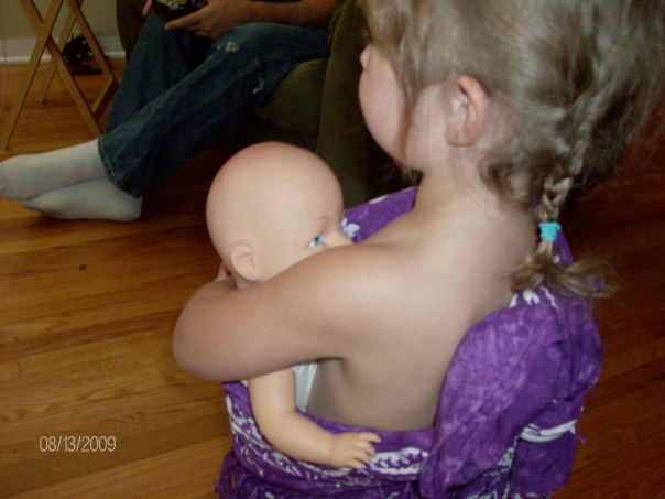 "Hannah, ""feeding"" her ""baby"" in a sling"